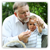 Photo of grandfather blowing bubbles with grandson