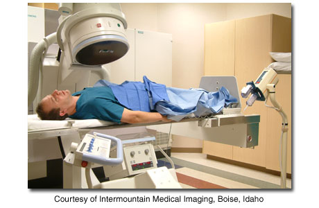 Person lying under X-ray machine in cath lab