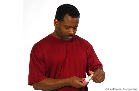 Picture of a man checking to make sure he has the correct medicine