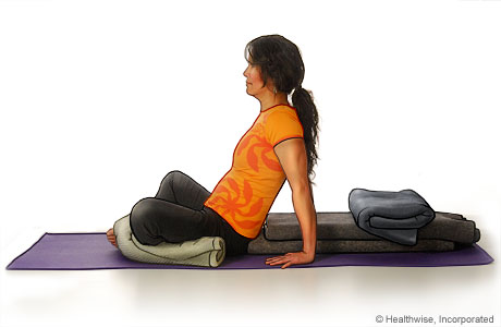 Picture of a woman in step five of reclining bound angle yoga pose