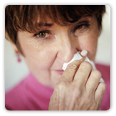 Photo of a woman with allergies holding a tissue to her nose