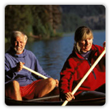 Older couple paddling canoe
